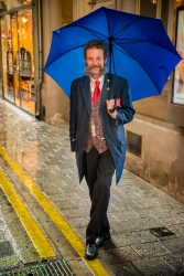 Sheltering from the rain underneath a blue umbrella in Vienna, Austria