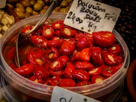 Red olives on display at Marché Raspail open air market, Paris, France