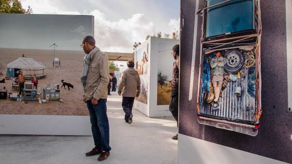A man stops to look at photographs displayed as part of the PhotoQuai 2013 Exhibition