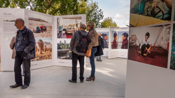 A couple looking at images in the PhotoQuai 2013 Exhibtion